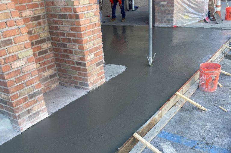 concrete sidewalk being installed in retail center